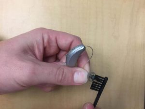 brushing off dust from a wet hearing aid