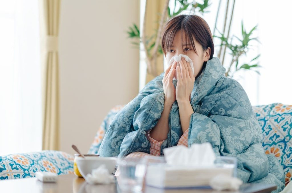 A woman feeling sick at home is blowing her nose with tissue papers.