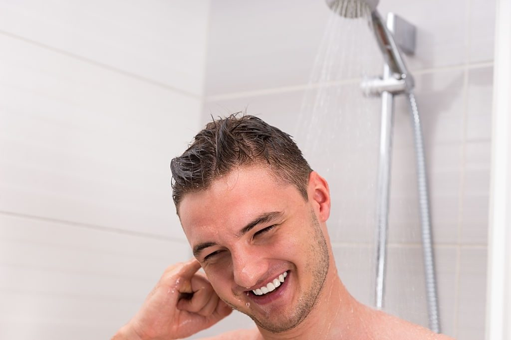 Young man cleaning his ear while taking a shower