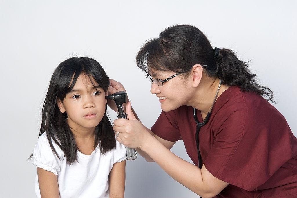 a female audiologist checking a girl's ear