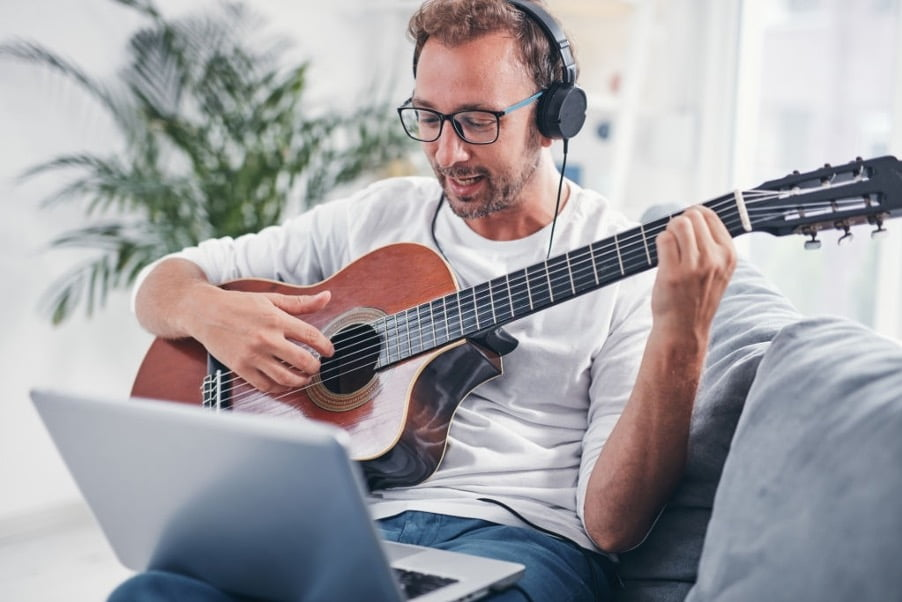 a guy wearing headphone and learning guitar