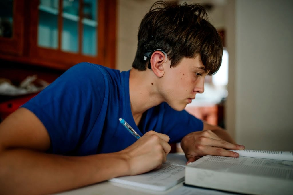 15 years old boy with cochlear implant doing homework