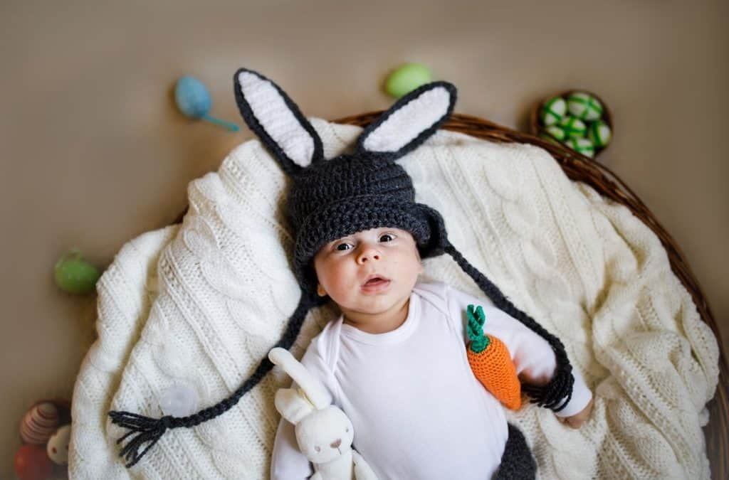 newborn baby boy wearing bunny ears and tail in a basket.
